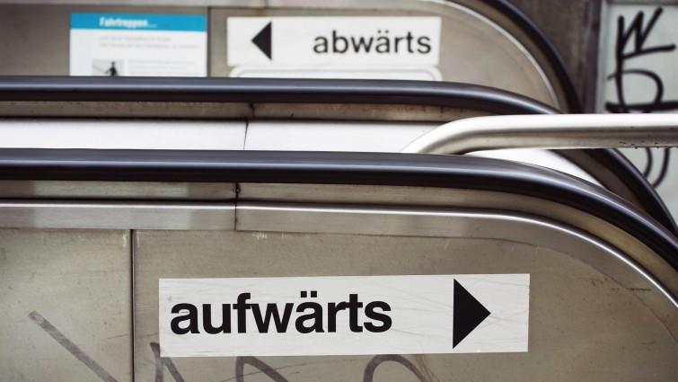 """Zwei Schilder mit den Aufschriften """"aufwärts"""" und """"abwärts"""" kleben an einer Rolltreppe (picture alliance / dpa, Wolfram Steinberg)"""